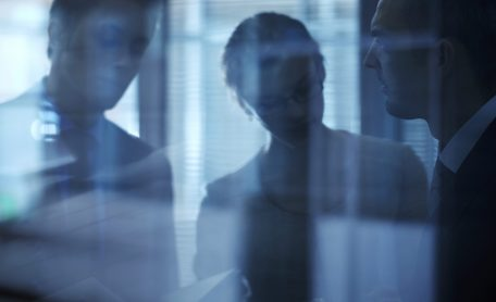 Blurred and darkened image of three office workers viewed through glass